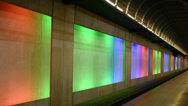 Underground subway rail with walls of neon colored lights